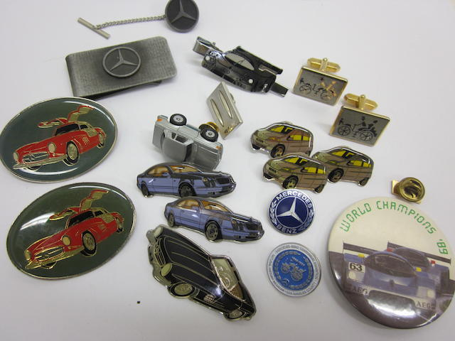 A collection of Mercedes-Benz pins, tie bars, and a money clip.