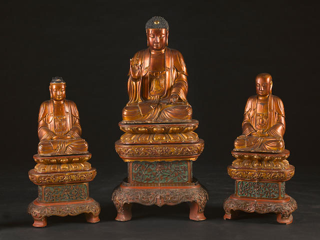 A large assembled gilt and red lacquered wood Buddhist triad  Qing dynasty elements
