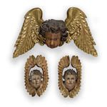 A pair of Spanish polychrome and gilt decorated carved wood amorini together with an Italian polychrome and gilt decorated carved wood amorini 18th century