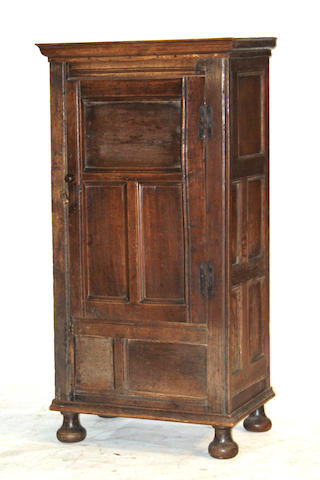 A Baroque style oak single door cupboard