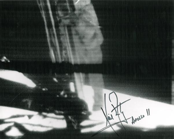 ARMSTRONG DESCENDS THE LADDER—SIGNED. Black and white photograph, 8 x 10 inches.