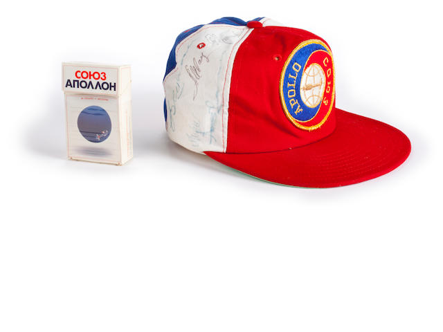 "ALEXEI LEONOV'S SIGNED ASTP BASEBALL CAP. Baseball cap with Apollo-Soyuz patch on front, cotton, manufactured by Toppers of Philadelphia. Together with an open pack of ""Apollo Soyuz"" cigarettes manufactured by Philip Morris, the design for the pack being by Alexei Leonov."