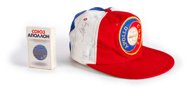 """ALEXEI LEONOV'S SIGNED ASTP BASEBALL CAP. Baseball cap with Apollo-Soyuz patch on front, cotton, manufactured by Toppers of Philadelphia. Together with an open pack of """"Apollo Soyuz"""" cigarettes manufactured by Philip Morris, the design for the pack being by Alexei Leonov."""