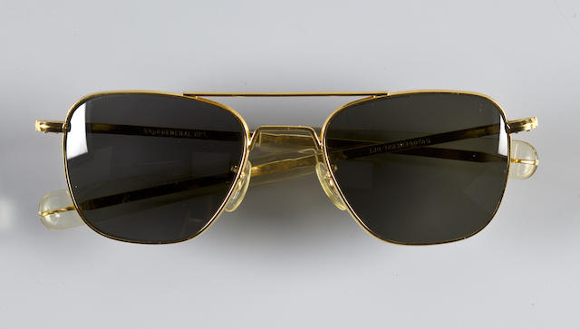 WALLY SCHIRRA'S PILOT SUNGLASSES. SCHIRRA ON SPORTS CARS AND MORE! Standard-issue military sunglasses by General Optical, in gold-colored metal with straight-prong supports and green-gray lenses.