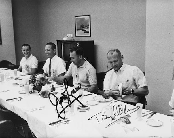 ASTRONAUTS AT LUNCH. Black and white photograph, 8 x 10 inches, with printed NASA text on verso. Framed.