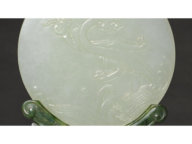 A circular white jade plaque with spinach jade stand