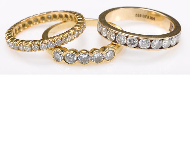 A collection of three diamond, 18k and 14k gold bands
