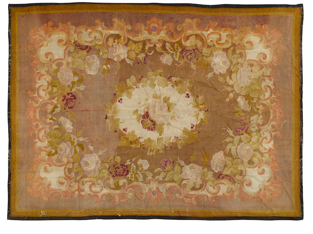 A Napoleon III Aubusson carpet, with a central medallion with roses surrounded by a border of roses and scrolls on a chocolate ground, 10 x 7.6ft
