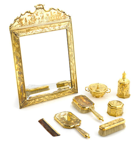 An Edwardian Queen Anne style chinoiserie decorated silver gilt vanity set