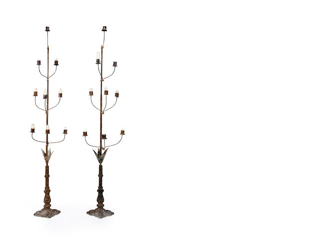 A pair of standing candelabrum, Italian circa 1890, with molded iron base with applied tin leaves and an iron shaft with 9 candle cups *** ESTIMATE TO FOLLOW
