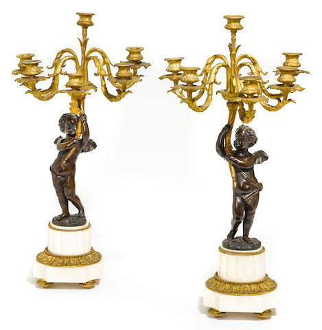 A pair of French gilt and patinated bronze and marble six light figural candelabra <BR />late 19th century
