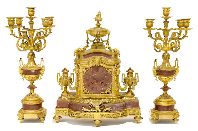 A French gilt bronze and rouge marble clock garniture <BR />early 20th century