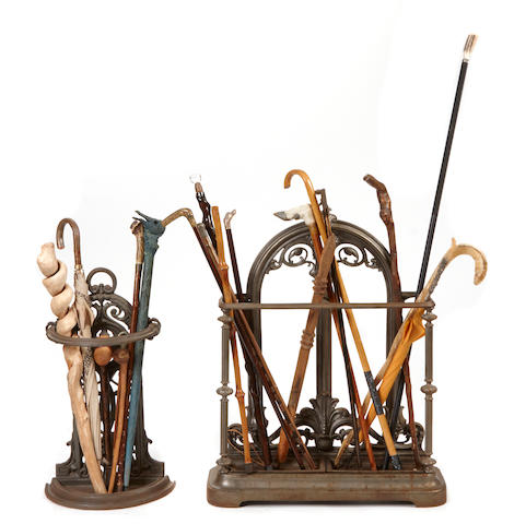 A collection of walking sticks with two cast-iron stands