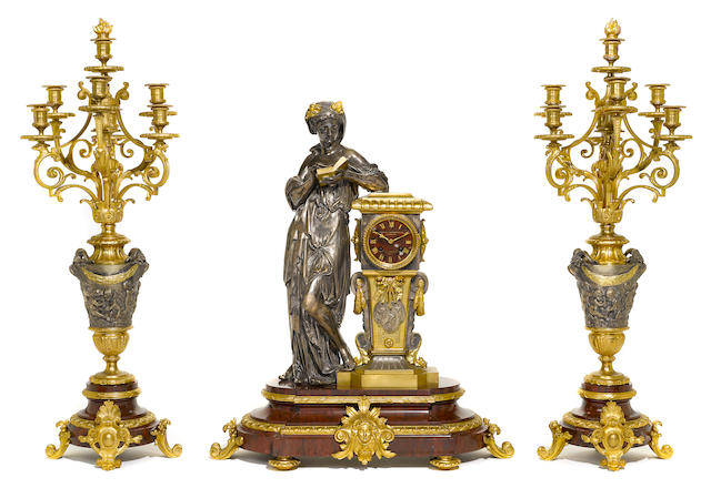A good quality French silvered and gilt bronze and rouge marble clock garniture <BR />second half 19th century