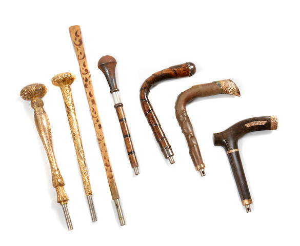 An assembled group of parasol handles and walking stick handles