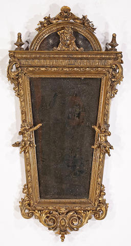 A Rococo style gilt metal and composition mirror late 19th/early 20th century