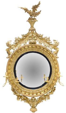 A good and imposing Regency parcel ebonized carved giltwood girandole <BR />first quarter 19th century