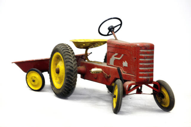 A vintage child size tractor with trailer,