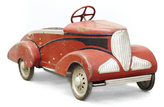 An antique childs pedal car,
