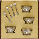 A set of four French  first standard silver  Art Nouveau salt cellars and spoons, with case maker's mark EN, retailed by F. Senn, Paris,  late 19th / early 20th century