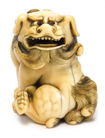 An ivory netsuke of a shish inscribed Tomotada