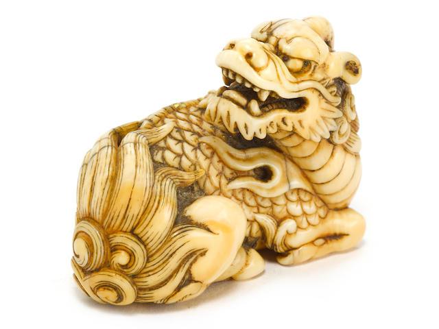 An ivory netsuke of a recumbent kirin by Okatomo