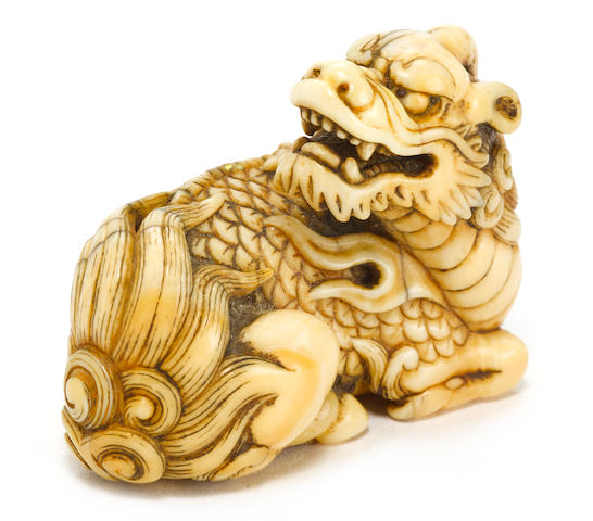 An ivory netsuke of a recumbent kirin By Okatomo, Kyoto, Edo period (late 18th/early 19th century)