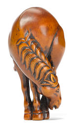 A wood netsuke of a standing horse