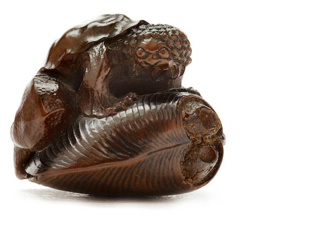 A wood netsuke of a kappa on a clamshell by Komin