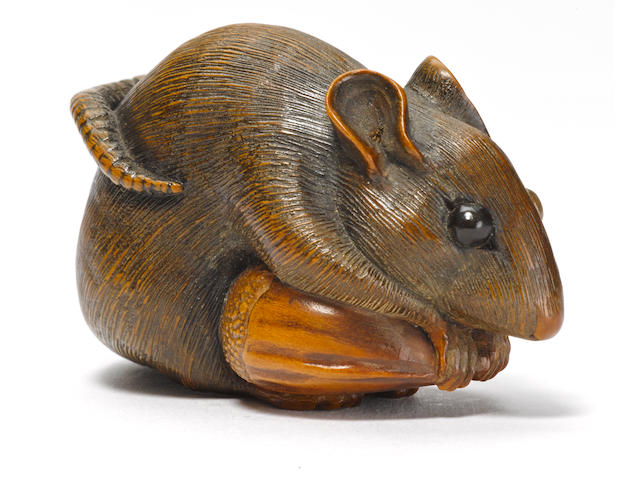 A wood netsuke of a rat on a chestnut by Goho