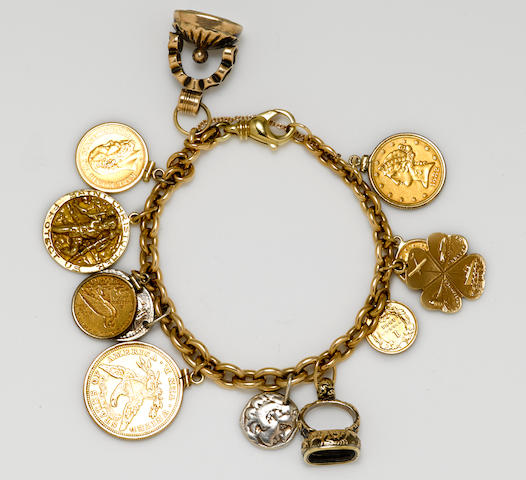A 14k gold charm bracelet suspending twelve gold coin, silver coin, rock crystal, 14k gold and metal charms
