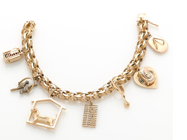 A 14k gold charm bracelet suspending six 14k gold and one 14k gold and gilt-silver charms