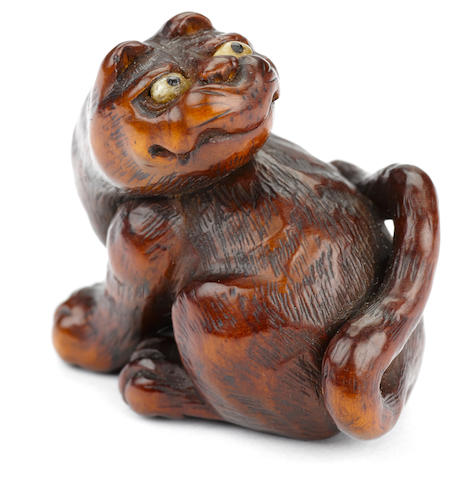 A wood netsuke of a tiger By Ichi...., late Edo/early Meiji (19th century)