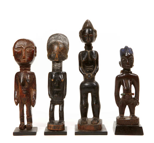 A group of four small African carved wooden figures