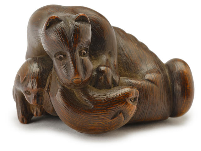 A wood netsuke of a bitch and two puppies