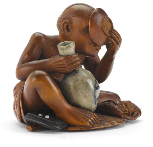 A wood and ceramic netsuke of a sake drinker By Keisai, Meiji period (late 19th century)
