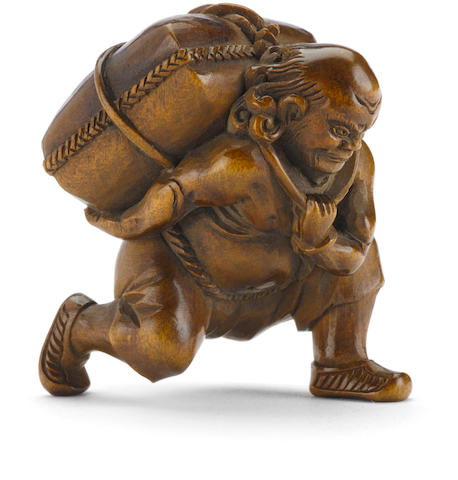A wood netsuke of a figure with a kappa in a parcel By Minkoku, Edo period (19th century)