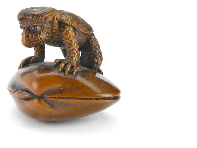 Wood netsuke of a kappa on a shell By Suketada