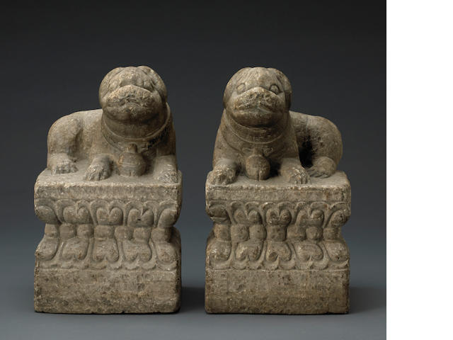 A pair of stone dogs on pedestals