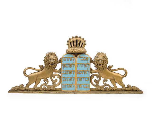 A paint-decorated, gilt-heightened, carved wooden ark pediment: gilded lions flanking the Decalogue attributed to the workshop of M. C. IllionsNew York City (lower east side), c.1920