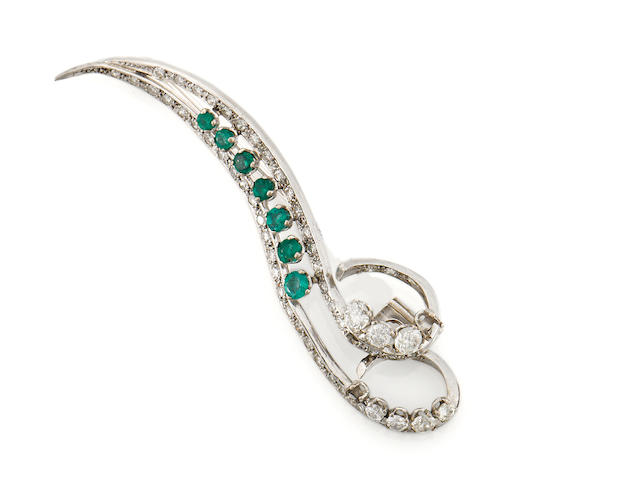 An emerald and diamond scroll brooch
