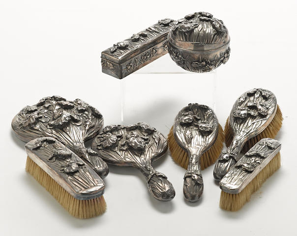A Japanese Export silver iris-repousse-decorated eight piece vanity set with character marks, circa 1900