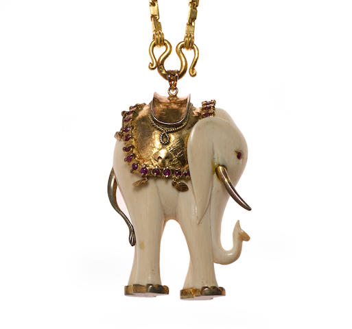 An ivory, ruby and gilt-silver elephant pendant with eighteen karat gold chain
