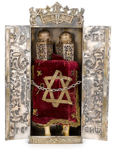 A 20th century silver Torah case with a late 19th century Italian Torah mounted on associated silver, wood, and bone rollers; in an associated silver case, 20th century, decorated in Polish style with flora and fauna.