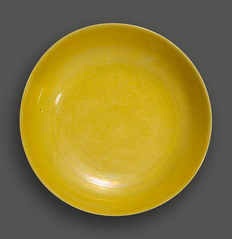 A yellow glazed dish with incised dragon decoration Daoguang mark and of the period