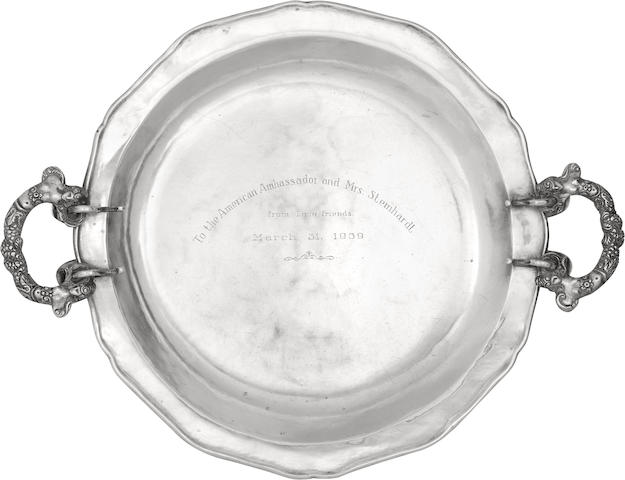 "A near pair of Peruvian silver two-handled chargers the first apparently unmarked, the underside of the second struck ""Juan 8215N Otello Lima"" within a triangular cartouche, circa 1939"