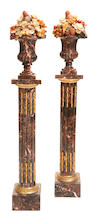 A pair of Neoclassical style brown and multi color marble flower and fruit filled urns on gilt bronze mounted brown marble pedestals