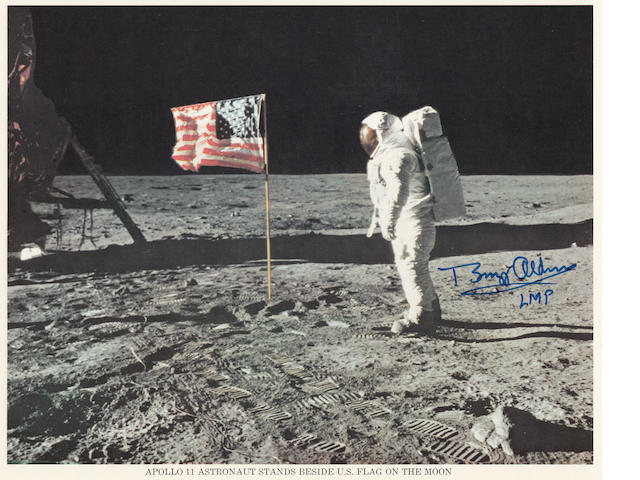 ALDRIN WITH THE STARS AND STRIPES ON THE LUNAR SURFACE.