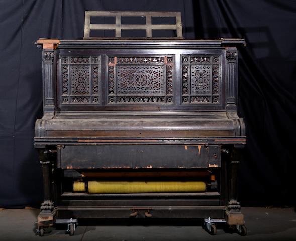 An upright player piano, circa 1900,