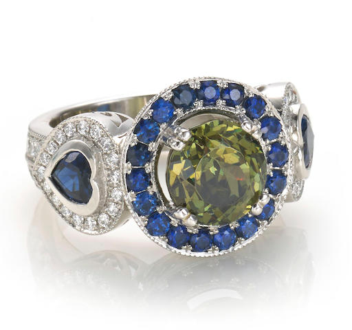 A color-change demantoid garnet, sapphire, diamond and chameleon diamond ring
